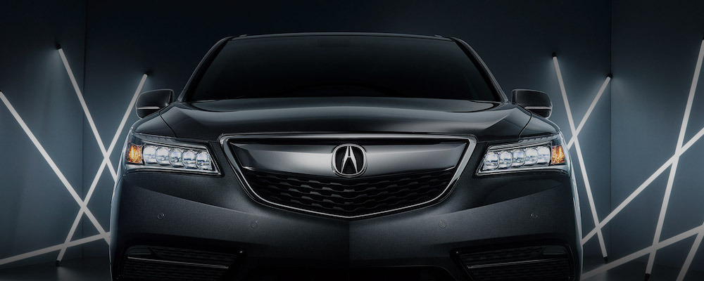 front view of gray or black acura with dark background and white lights