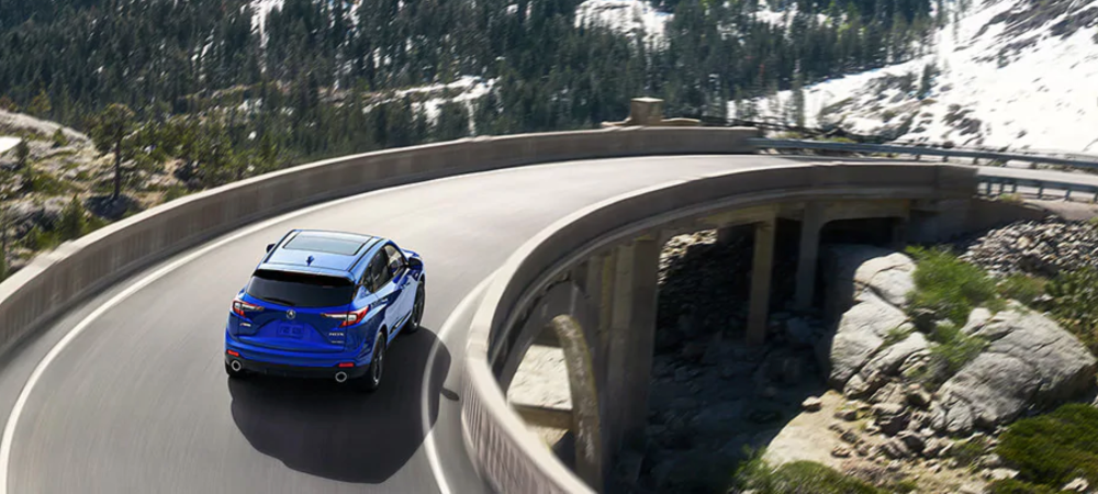 Blue 2020 Acura RDX driving through mountains